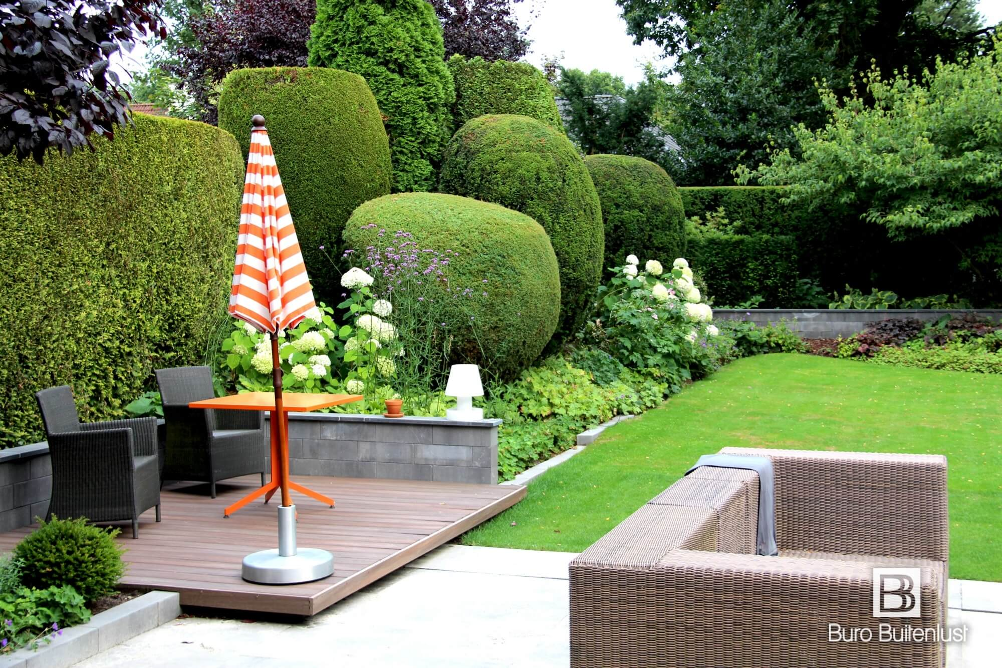Tuinmuurtjes en terrassen laten deze landschappelijke tuin nog beter aansluiten bij de moderne architectuur van dit woonhuis in Eindhoven